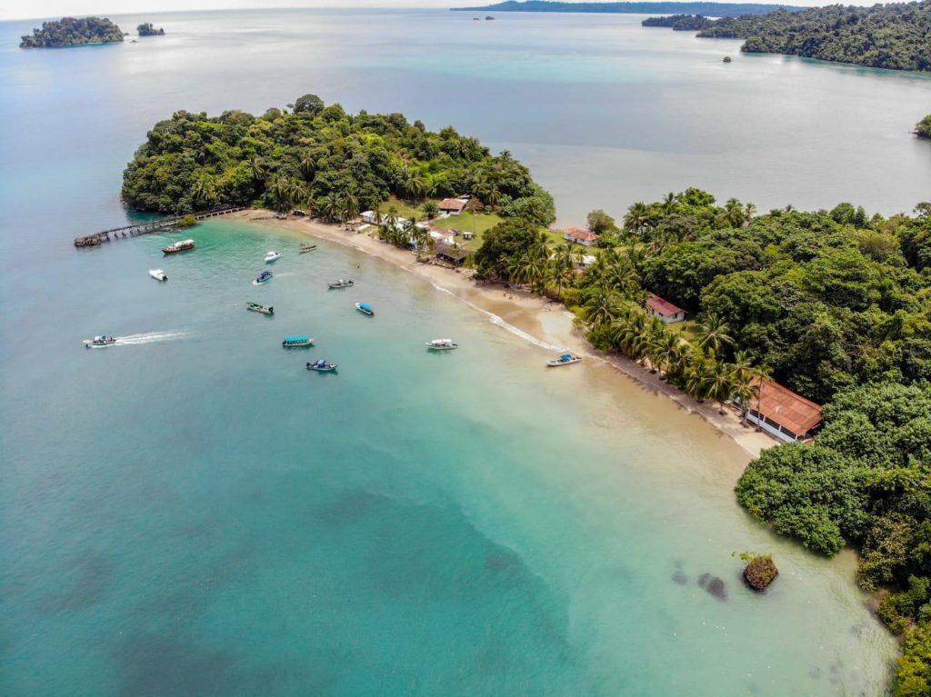 Imagen aerea de una parte de la isla de Coiba donde se aprecia vegetación y una impresionante playa de arena blanca y aguas cristalinas con azul turquesa